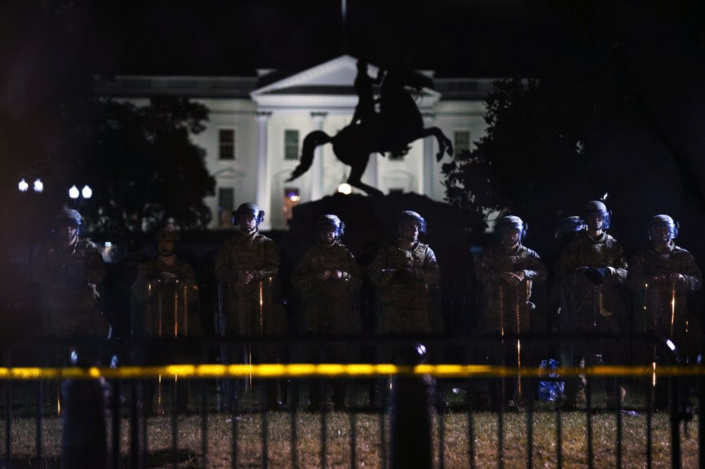 With the White House in the background, a line of police forms behind a fence in Lafayette Park as demonstrators gather to protest the death of George Floyd, Tuesday, June 2, 2020, in Washington.