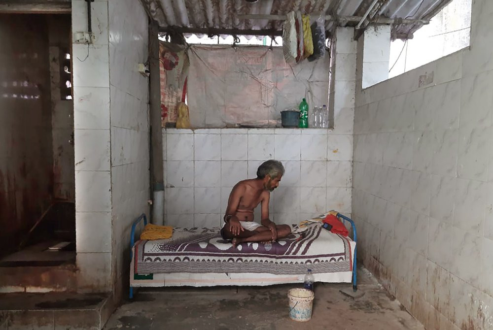Raja Kadam rests on his bed inside a toilet complex in Dharavi, one of Asia's largest slums, in Mumbai, India, Saturday, May 16, 2020.
