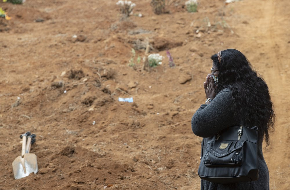 Vera Lucia Souza stands before at the gravesite of her 47-year-old brother Paulo Roberto da Silva, who died of COVID-19, during his burial at the Sao Luiz cemetery in Sao Paulo, Brazil, Thursday, June 4, 2020.