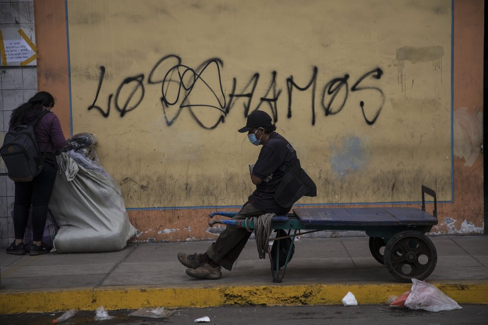 A porter rests on his cart amid the new coronavirus pandemic, in La Victoria district of Lima, Peru, Friday, June 19, 2020.