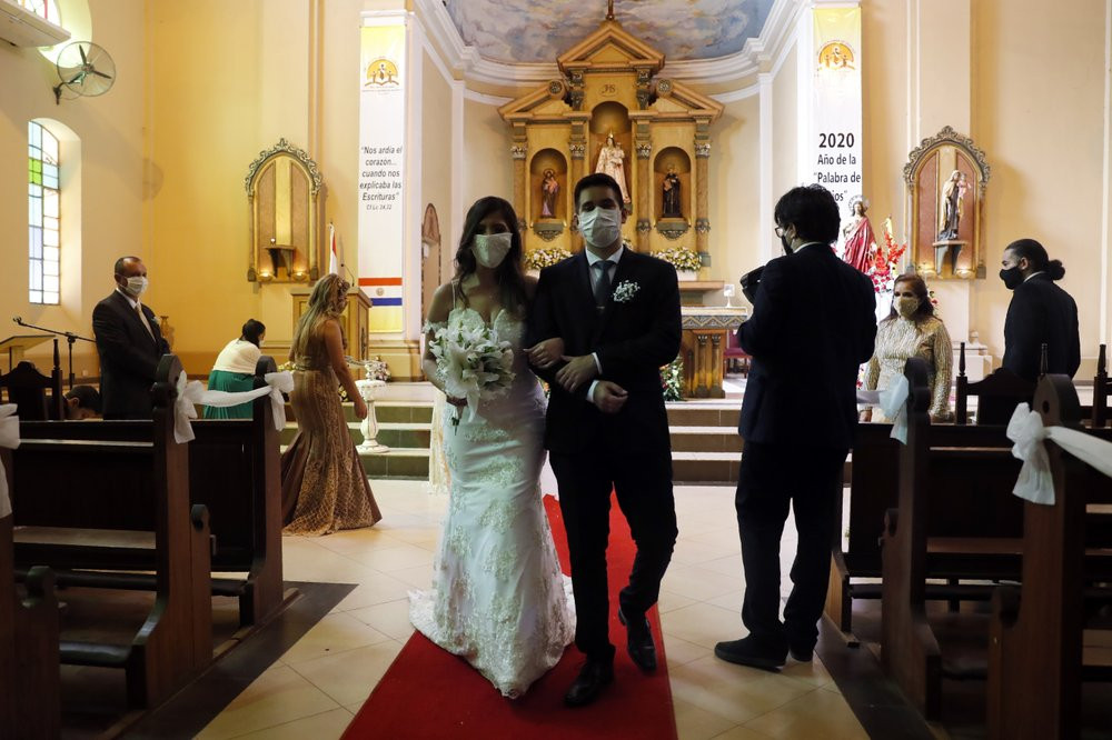 Bride Jazmin Sanabria and her groom Joel Adorno, wearing protective face masks amid the new coronavirus pandemic, walk down the aisle in the first wedding ceremony since 101 days of quarantine at the Virgen del Rosario church, in Luque, Paraguay.
