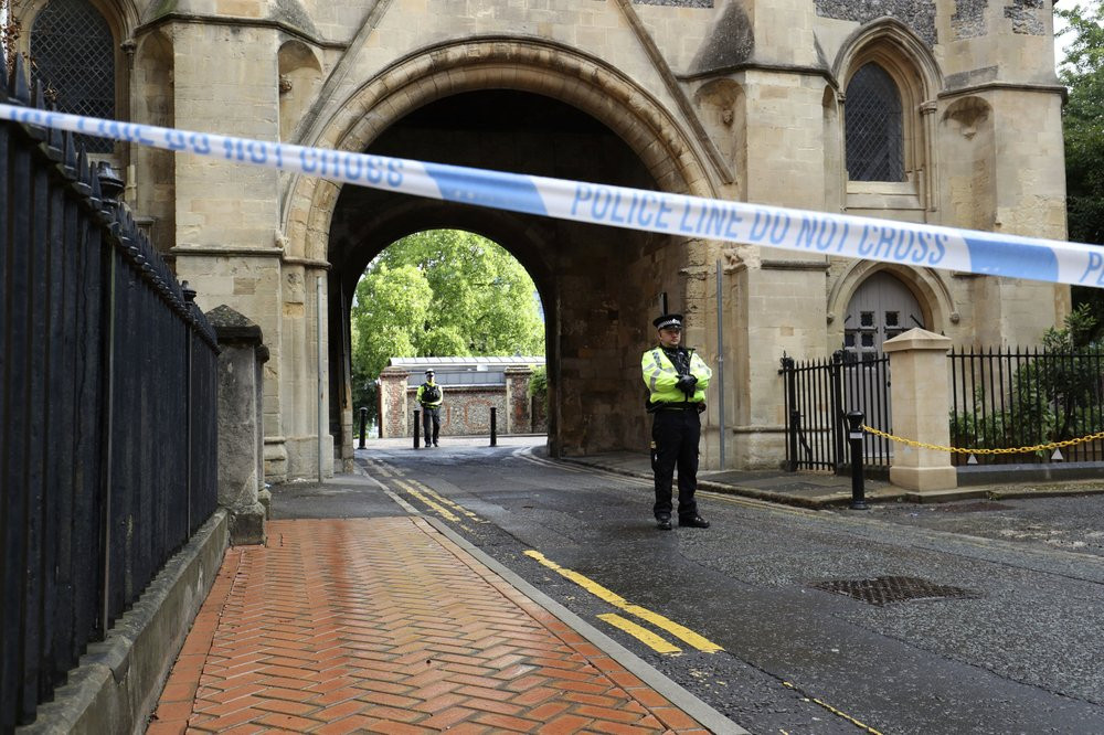 Police stand guard at the Abbey gateway of Forbury Gardens park in Reading town centre following Saturday's stabbing attack in the gardens, Sunday June 21, 2020.
