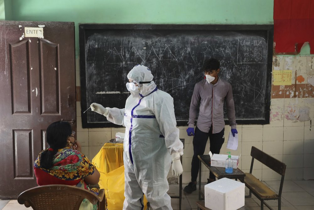 In this Wednesday, June 24, 2020, photo, a health worker takes a swab sample of a woman for a COVID-19 test in New Delhi, India.
