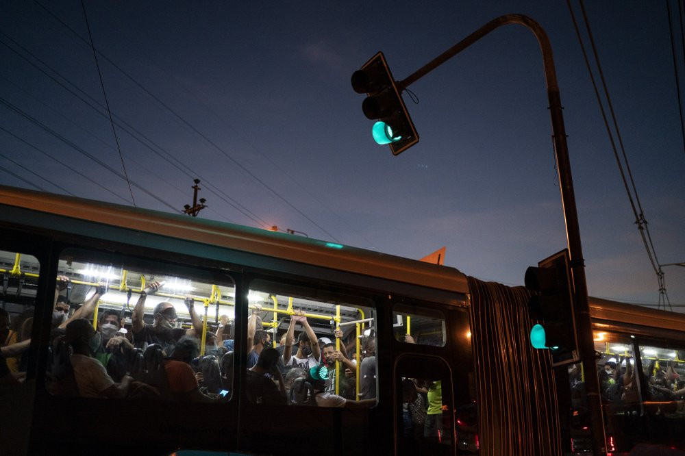 Commuters, some wearing protective face masks, ride a bus amid the new coronavirus pandemic in Rio de Janeiro, Brazil, Thursday, June 25, 2020.