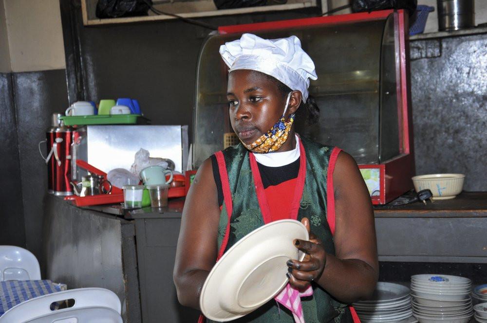 In this photo taken Saturday, June 20, 2020, Rebecca Nakamanya works at a restaurant near a bus terminal in capital Kampala, Uganda.