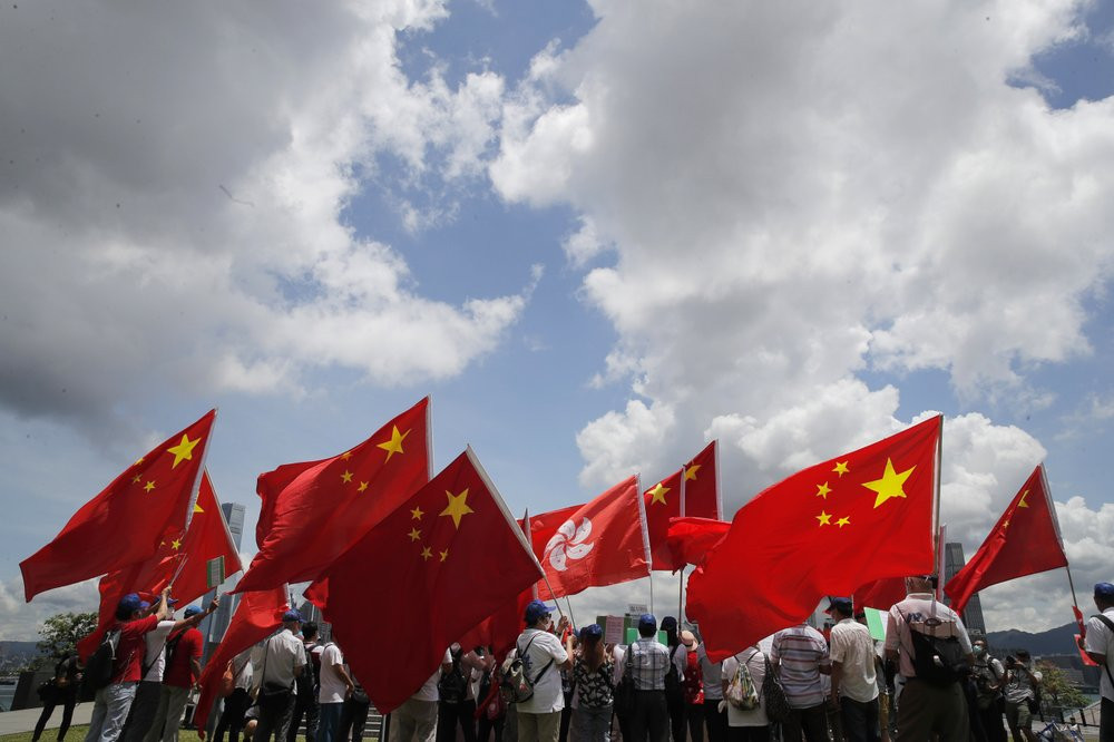 Pro-China supporters hold Chinese and Hong Kong national flags during a rally to celebrate the approval of a national security law for Hong Kong, in Hong Kong, Tuesday, June 30, 2020.