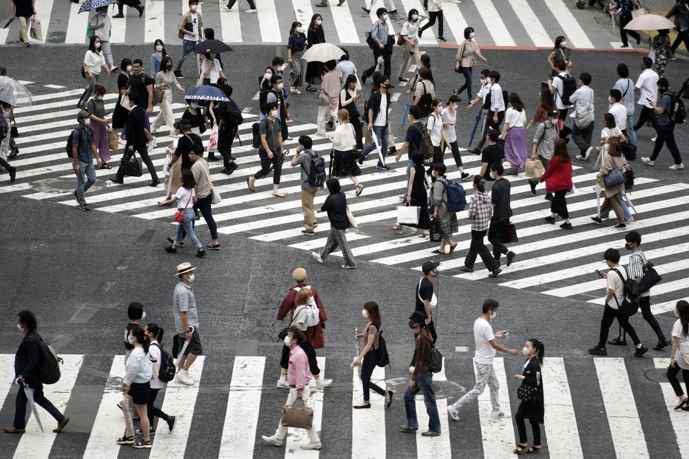 People wearing a protective face mask to help curb the spread of the coronavirus walk at Shibuya pedestrian crossing Thursday, July 9, 2020, in Tokyo.