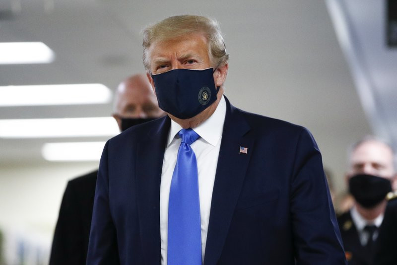 US President Donald Trump wears a mask as he walks down the hallway during his visit to Walter Reed National Military Medical Center in Bethesda, Md., Saturday, July 11, 2020.