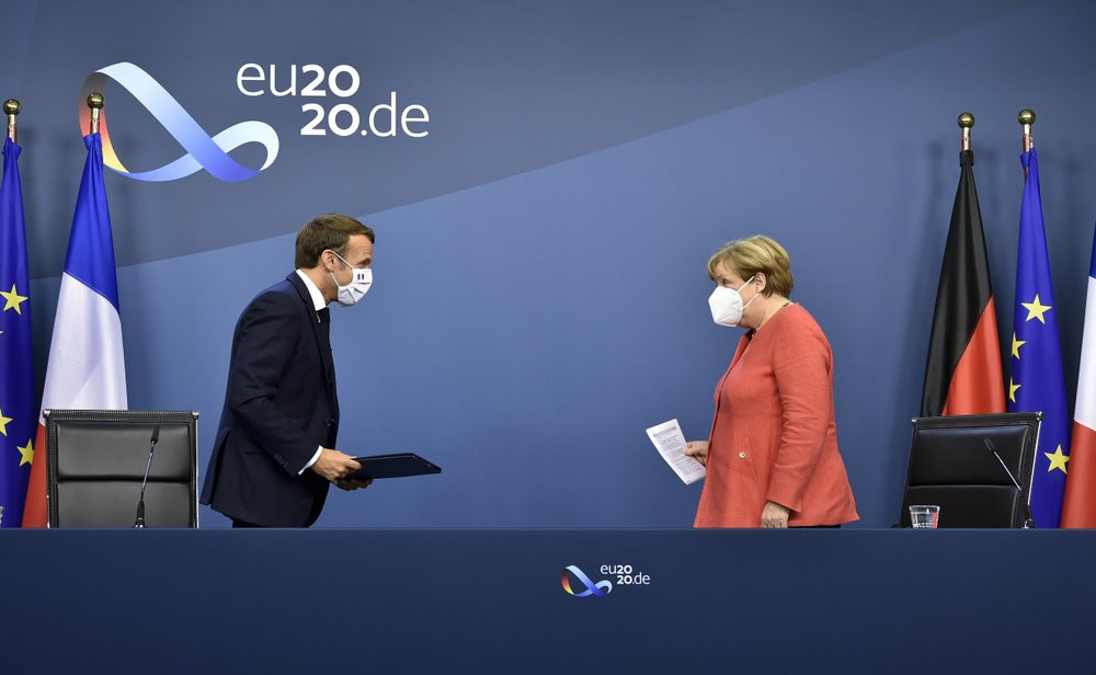 German Chancellor Angela Merkel, right, and French President Emmanuel Macron prepare to address a media conference at the end of an EU summit in Brussels, Tuesday, July 21, 2020.
