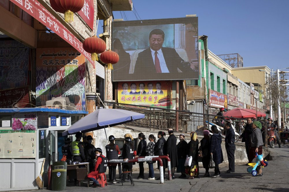In this Nov. 3, 2017, file photo, residents line up at a security checkpoint into the Hotan Bazaar where a screen shows Chinese President Xi Jinping in Hotan in western China's Xinjiang region.