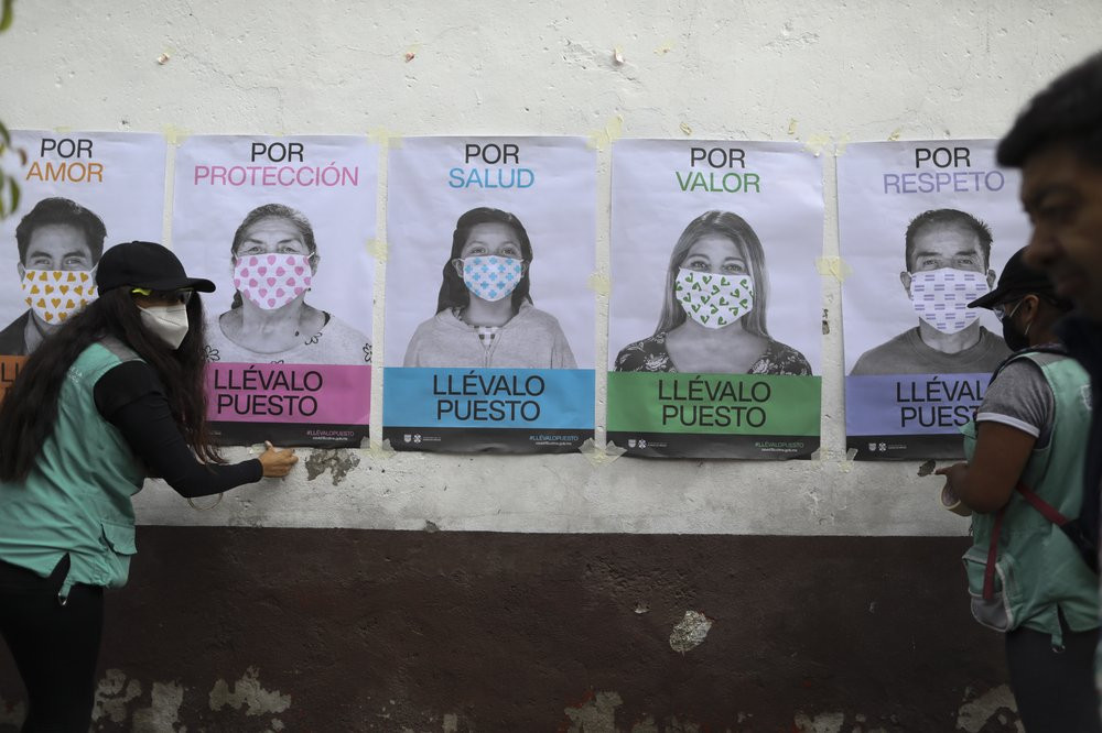A man not wearing a face mask walks by as city health department workers affix a series of posters advocating mask use to a wall, in San Mateo Xalpa in the Xochimilco district of Mexico City, Tuesday, July 21, 2020.