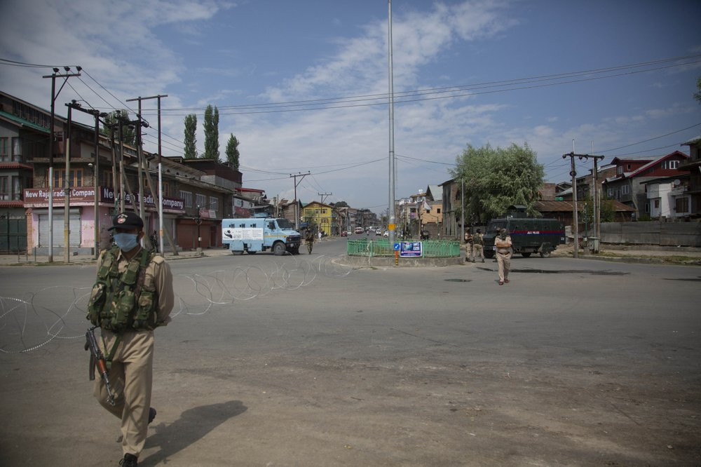 Policemen and paramilitary soldiers patrol a road during curfew in Srinagar, Indian controlled Kashmir, Tuesday, Aug. 4, 2020.