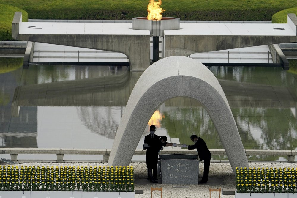 Kazumi Matsui, right, mayor of Hiroshima, and the family of the deceased bow before they place the victims list of the Atomic Bomb at Hiroshima Memorial Cenotaph.