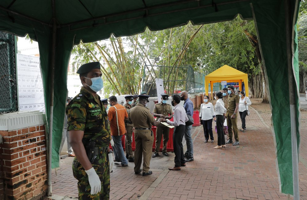 A Sri Lankan government soldier stands guard at the entrance to a ballot counting center as workers show their identity to police officers, a day after voting for general elections in Colombo, Sri Lanka, Thursday, Aug. 6, 2020.