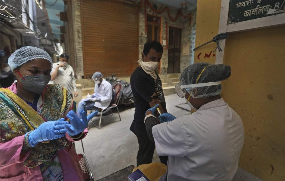 Health workers take blood samples for a random serological test to check for antibodies against the coronavirus in New Delhi, India, Thursday, Aug. 6, 2020.