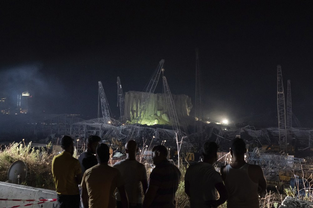 People look at the scene of Tuesday's explosion that hit the seaport of Beirut, Lebanon, Friday, Aug. 7, 2020.