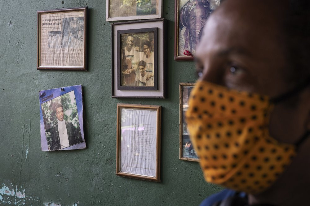 Marcio Antonio do Nascimento stands next to a framed childhood image of his 25-year-old son Hugo do Nascimento who died from the new coronavirus, in Rio de Janeiro, Brazil, Saturday, Aug. 1, 2020.