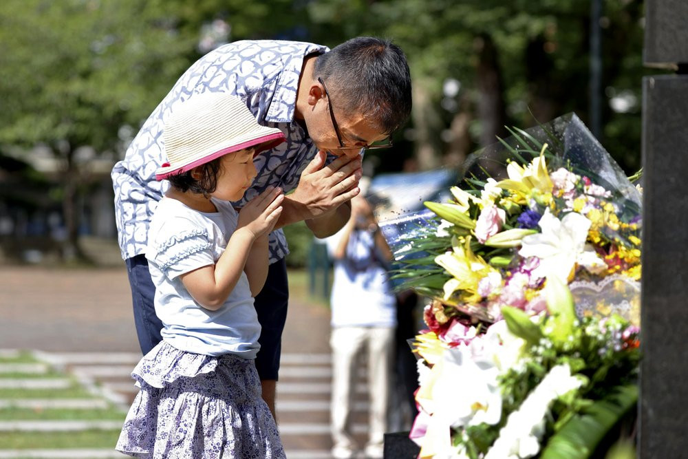 A man and his daughter pray for the victims of U.S. atomic bombing at the Atomic Bomb Hypocenter Park in Nagasaki, southern Japan, Sunday, Aug. 9, 2020.