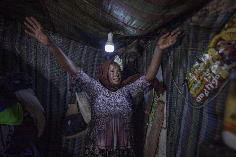 Mother of two Amsale Hailemariam, a domestic worker who lost work because of the coronavirus, stands in her small tent in the capital Addis Ababa, Ethiopia on Friday, June 26, 2020.