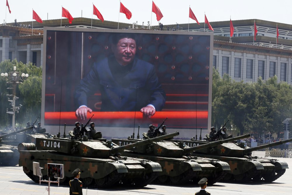In this Thursday, Sept. 3, 2015 file photo, Chinese President Xi Jinping is displayed on a screen as Type 99A2 Chinese battle tanks take part in a parade commemorating the 70th anniversary of Japan's surrender during World War II.