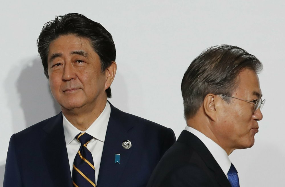 In this June 28, 2019, file photo, South Korean President Moon Jae-in, right, walks by Japanese Prime Minister Shinzo Abe upon his arrival for a welcome and family photo session at the G-20 leaders summit in Osaka, western Japan.