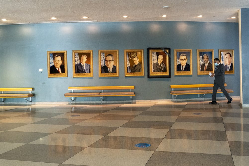 A man walk past portraits of former United Nations Secretary-Generals, Monday, Sept. 21, 2020 at United Nations headquarters.