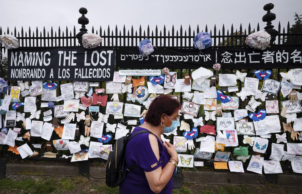 In this May 28, 2020, file photo, a woman passes a fence outside Brooklyn's Green-Wood Cemetery adorned with tributes to victims of COVID-19 in New York.