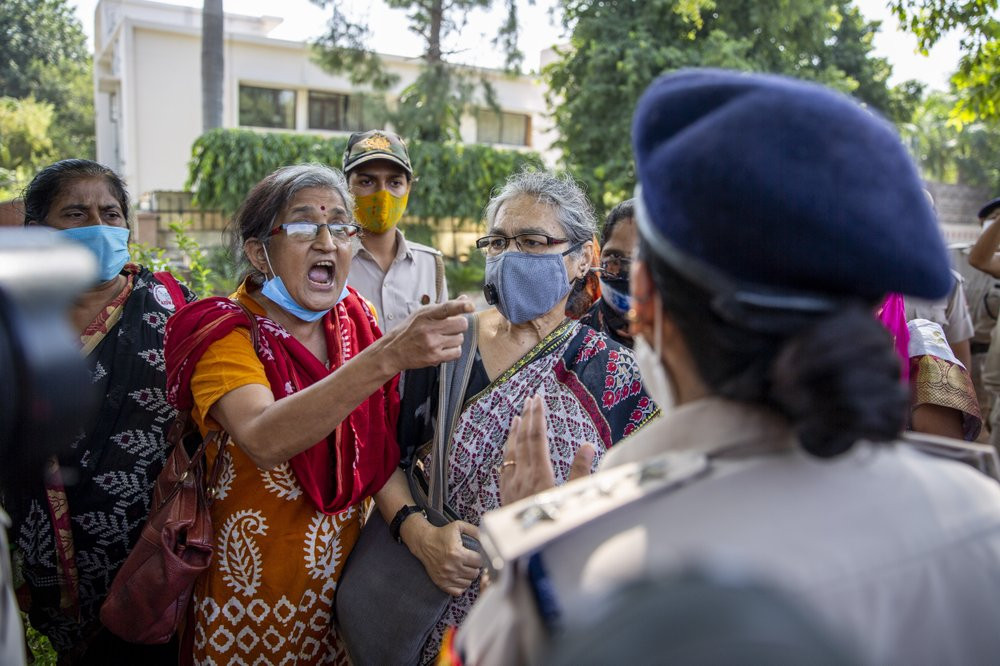 An Indian activist argues with a police officer before being detained by police during a protest in New Delhi, India, Wednesday, Sept. 30, 2020.