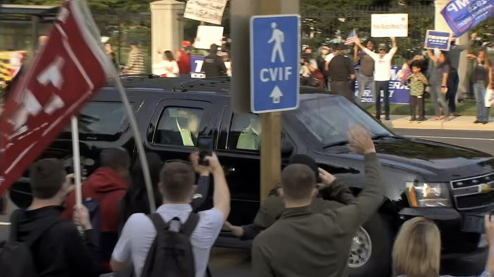In this image from video, President Donald Trump waves as he drives past supporters gathered outside Walter Reed National Military Medical Center in Bethesda, Md., Sunday, Oct. 4, 2020.