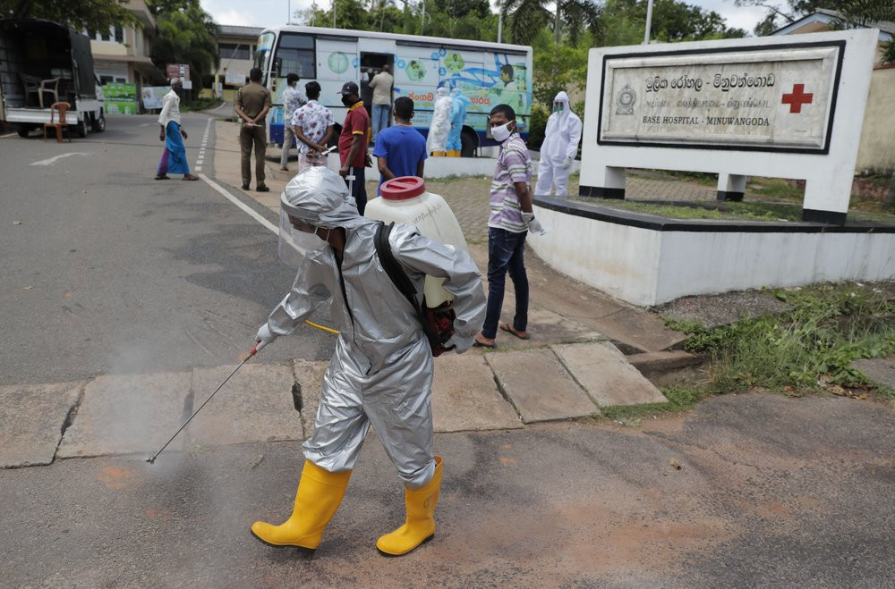 A Sri Lankan health worker sprays disinfectants as people wait to give swab samples to test for COVID-19 near a mobile testing vehicle outside a hospital in Minuwangoda, Sri Lanka, Tuesday, Oct. 6, 2020.