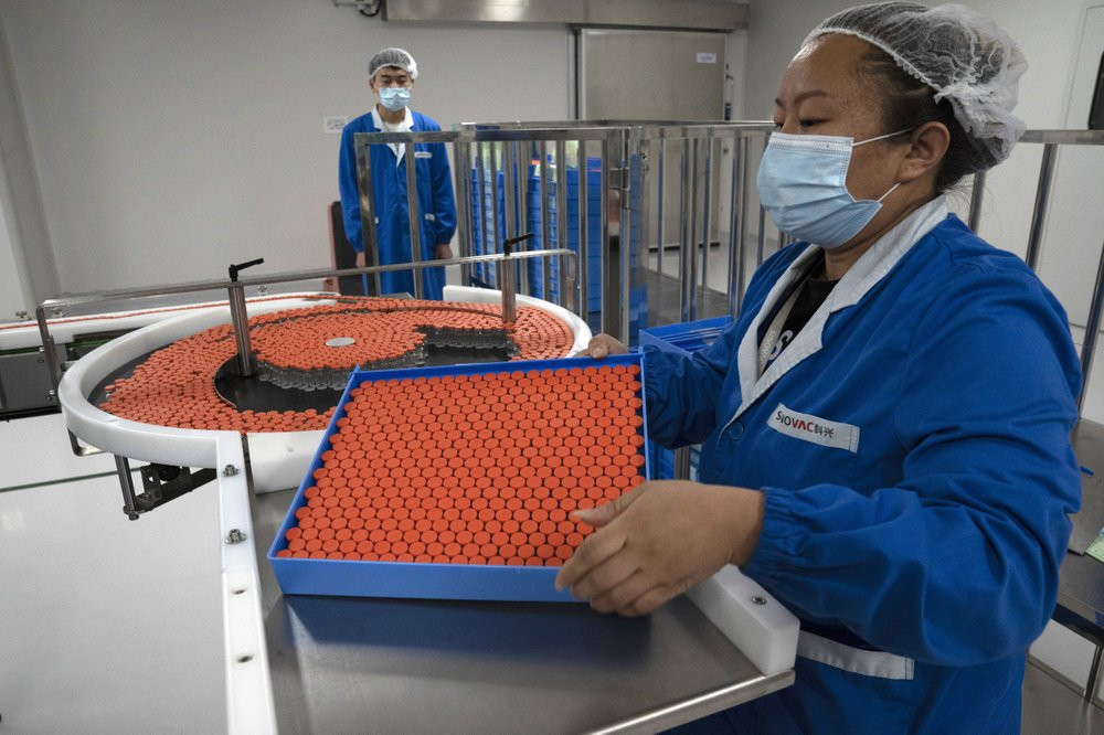 In this Sept. 24, 2020, file photo, a worker feeds vials for production of SARS CoV-2 Vaccine for COVID-19 at the SinoVac vaccine factory in Beijing.