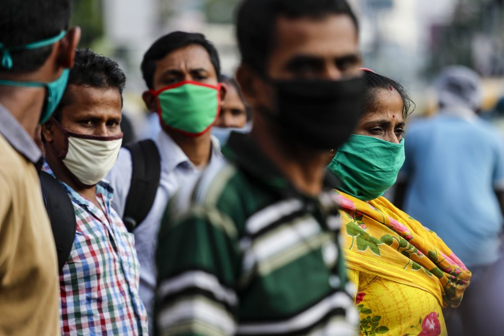 Commuters wearing face masks as a precautionary measure against the coronavirus wait for a bus in Kolkata, India, Saturday.