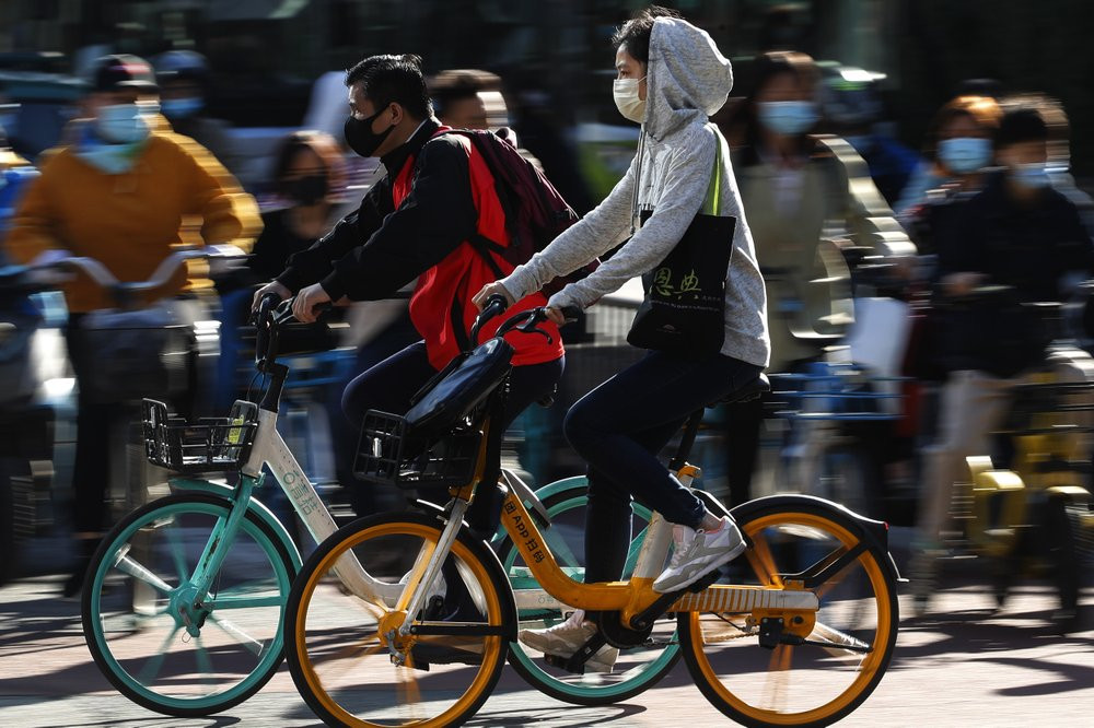 People wearing face masks to help curb the spread of the coronavirus ride bicycle during the morning rush hour in Beijing, Monday, Oct. 12, 2020.