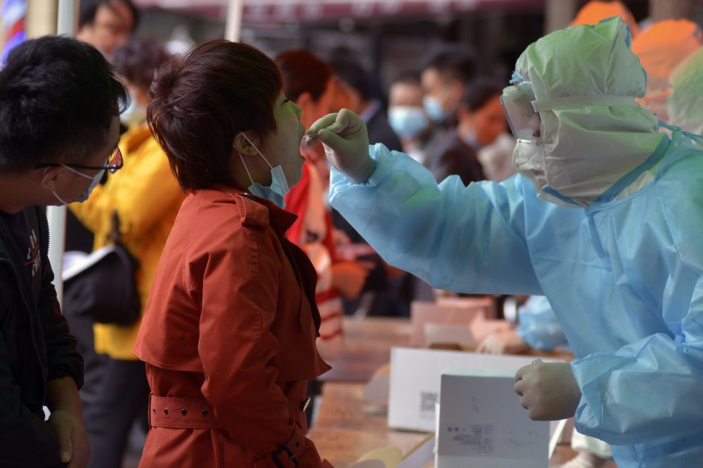 A medical staff takes a swab from a woman as residents line up for the COVID-19 test near the residential area in Qingdao in east China's Shandong province on Monday, Oct. 12, 2020.