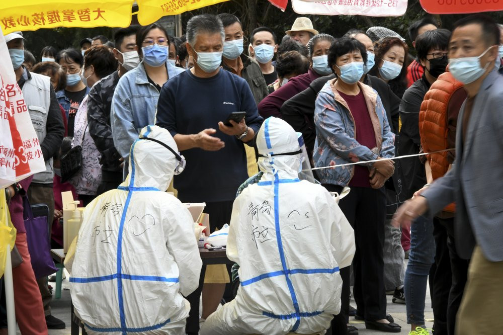 In this photo released by Xinhua News Agency, residents wearing face masks to help curb the spread of the coronavirus line up for the COVID-19 test near the residential area in Qingdao in east China's Shandong province on Tuesday.