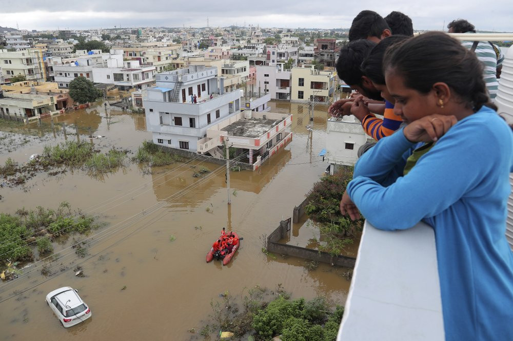 Residents look at a street inundated with floodwater after heavy rainfall in Hyderabad, India, India, Wednesday, Oct. 14, 2020.