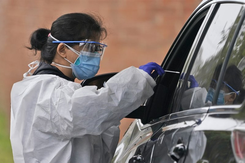 Medical personnel prepare to administer a COVID-19 swab at a drive-through testing site in Lawrence, N.Y., Wednesday, Oct. 21, 2020.