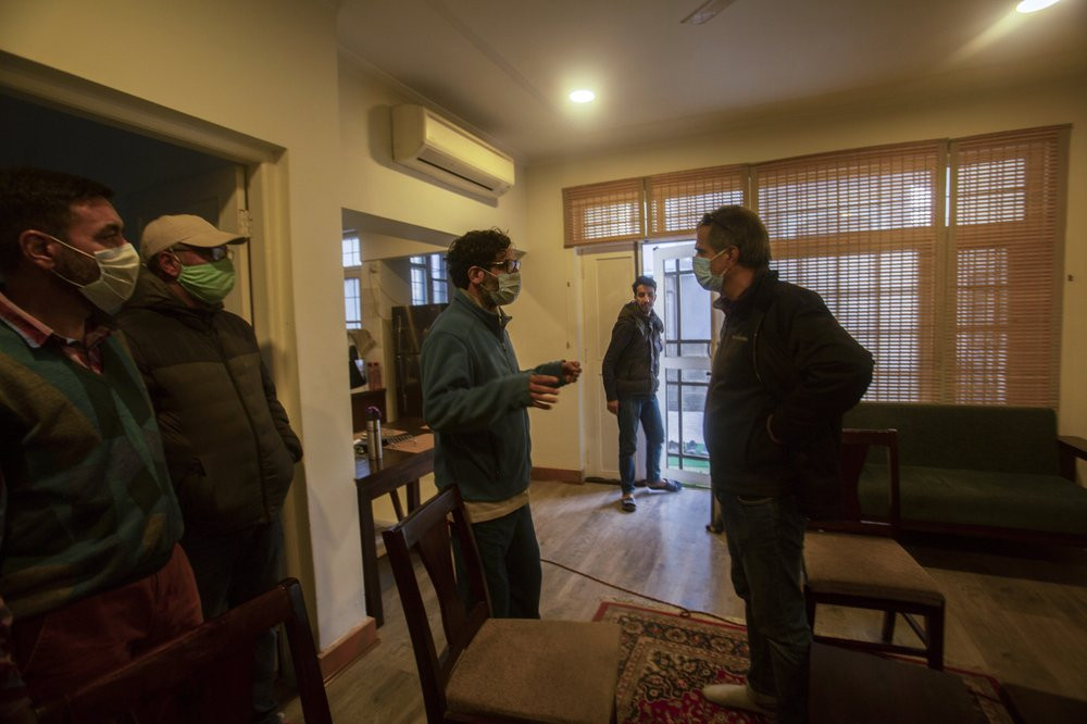 Agence France-Presse's Kashmir correspondent Parvaiz Bukhari, centre, talks to his colleagues after National Investigation Agency personnel searched his premises on the outskirts of Srinagar, Indian controlled Kashmir, Wednesday, Oct. 28, 2020.