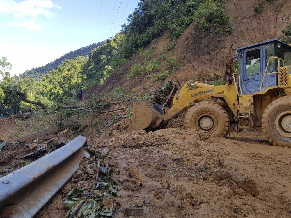 A bulldozer clears out the road damaged by landslide to access a village swamped by another landslide in Quang Nam province, Vietnam on Thursday, Oct. 29, 2020.