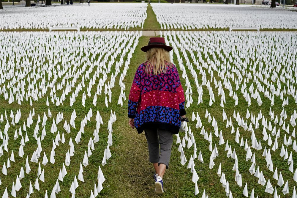 In this Oct. 27, 2020, Artist Suzanne Brennan Firstenberg walks among thousands of white flags planted in remembrance of Americans who have died of COVID-19 near Robert F. Kennedy Memorial Stadium in Washington.