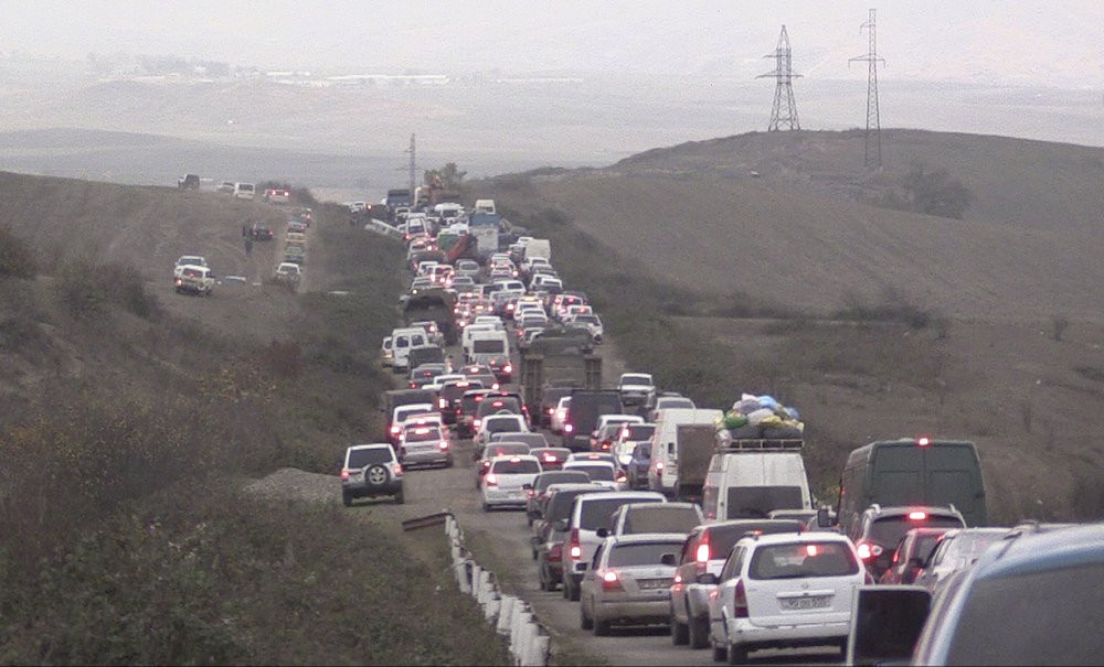 In this photo taken from the Associated Press Television video, people stuck in a traffic jam as they leave the separatist region of Nagorno-Karabakh to Armenia, Saturday, Nov. 7, 2020.