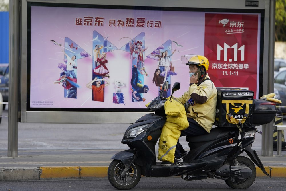 A delivery man passes by an ad for the Nov. 11 Sales Day in Beijing, China on Oct. 28, 2020.