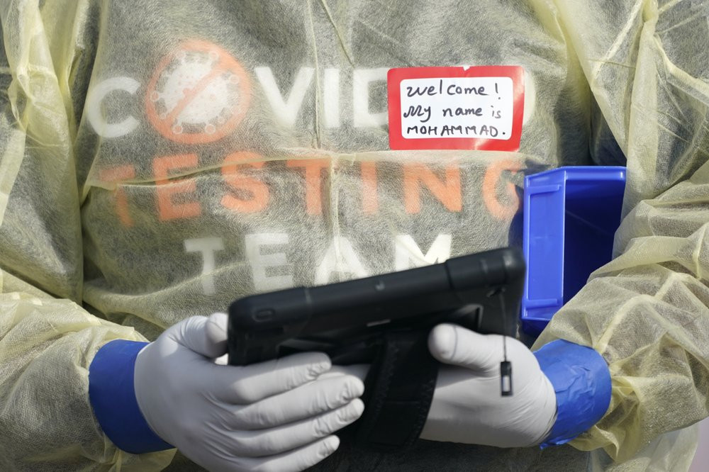 In this Oct. 28, 2020, file photo, a worker wearing gloves, and other PPE holds a tablet computer as he waits to check people at a King County coronavirus testing site in Auburn, Wash., south of Seattle.