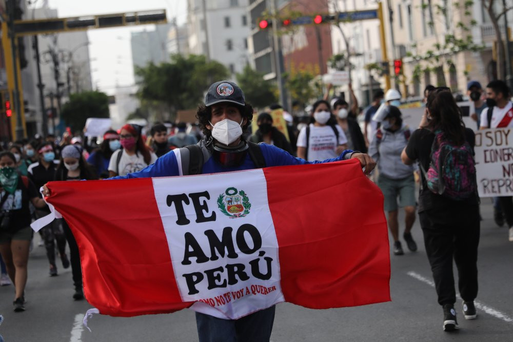 A supporter of ousted President Martin Vizcarra holds a banner with a message that reads in Spanish,