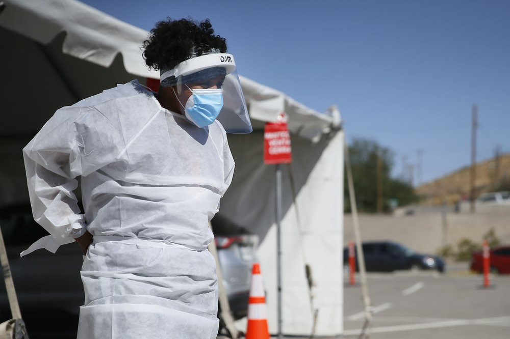 In this Oct. 26,2020, file photo, a medical worker stands at a COVID-19 state drive-thru testing site at UTEP, in El Paso, Texas.