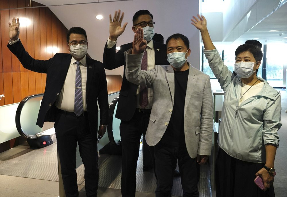 Pro-democracy legislators, from right, Wong Pik Wan, Wu Chi Wai, Lam Cheuk-ting, Yoon Siu Kin wave after handing their letters at Legislative Council in Hong Kong, Thursday day, Nov. 12, 2020.