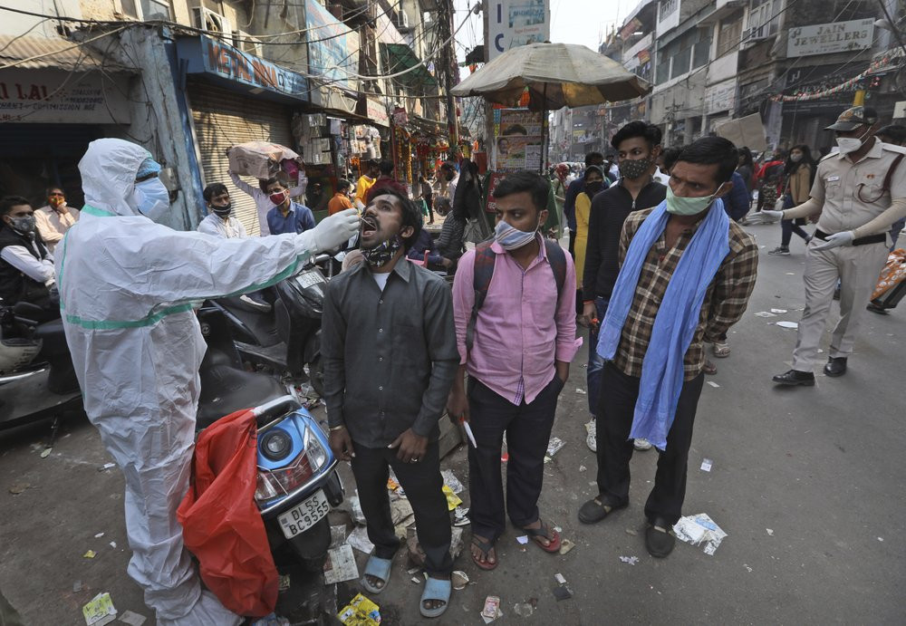 A health worker takes a sample to test for COVID-19 test at a market place in New Delhi, India, Thursday, Nov. 19, 2020.