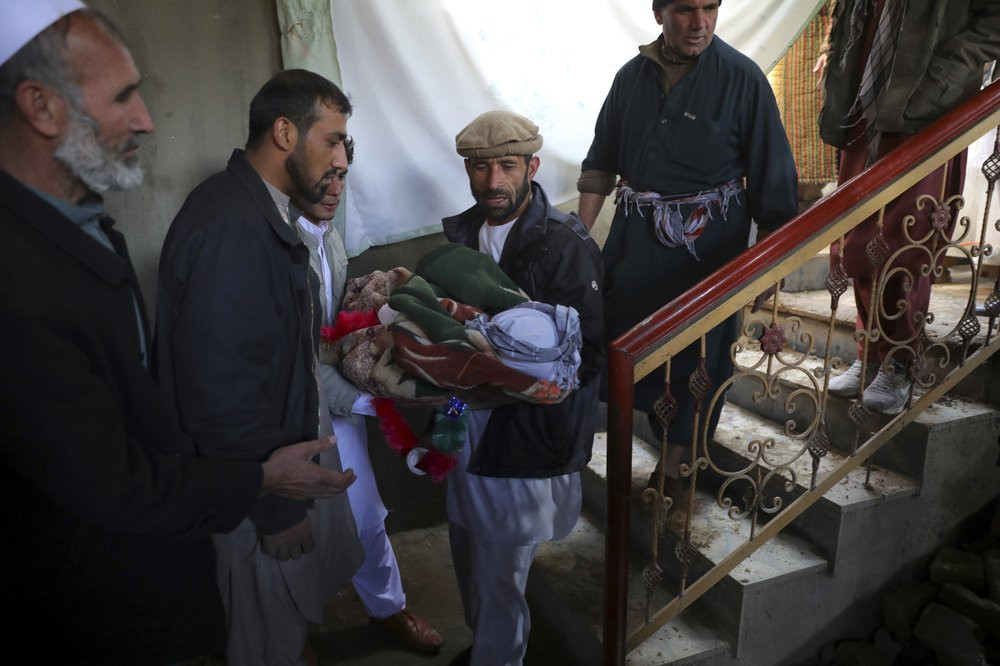 Relatives carry the dead body of a boy who was killed by a mortar shell attack in Kabul, Afghanistan, Saturday, Nov. 21, 2020. Mortar shells slammed into different parts of the Afghan capital on Saturday.