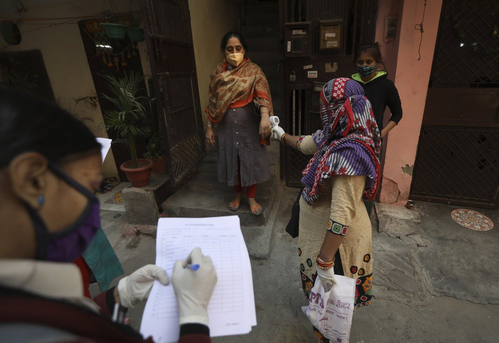 A health worker reads the temperature of a woman during a door to door survey to assess the COVID-19 situation in New Delhi, India, Monday, Nov. 23, 2020.