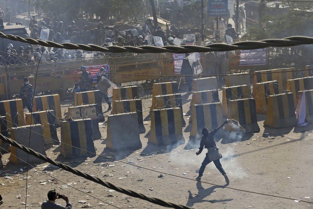 A farmer throws back a tear gas shells towards policemen, at the border between Delhi and Haryana state, Friday, Nov. 27, 2020.